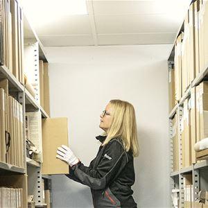 Arkivarie Sofia Hedén i museets arkiv bland hyllor med arkivkapslar och pärmar.
