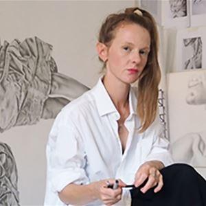 Konstnär Josefin Lindskog sitter framför några stora teckningar.