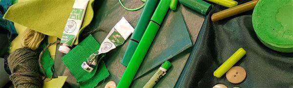 Pennor, färg, papper, tyg, knappar, garn - allt i grönt.