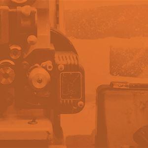 Del av gammal filmprojektor med rödbrunt filter.