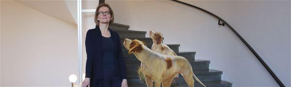 Intendent Ingela Broström i museets trappa med inklippta hundar från målning.