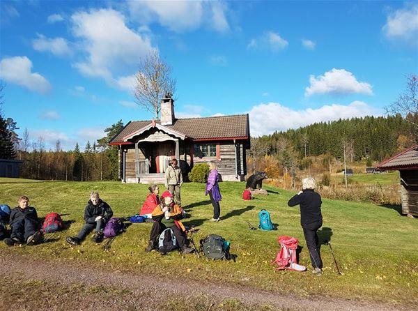 Personer med ryggsäckar sitter och står på gräsmattan framför en liten timmerstuga.