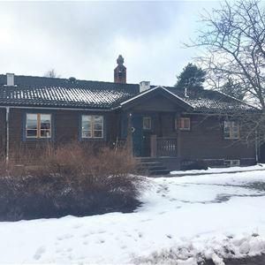 Exteriör vinter på ett brunt timmerhus, enplan med snötäckt gräsmatta framför.
