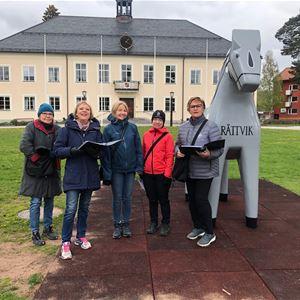 Några personer vid den grå Rättvikshästen utanför Rättviks Kommunhus.