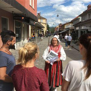 Guide i folkdräkt på gågatan informerar några deltagare.