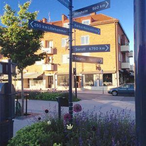 Centrum med ett torg och en vägskylt som visar åt olika håll.
