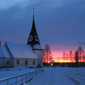 Kyrkan vid solnedgång med snö runt omkring.