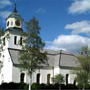Sollerö kyrka, exteriört. Vit kyrka med grönska omkring.
