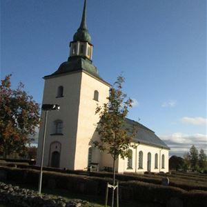 Våmhus kyrka exteriört med stenmur framför. Grönska omkring.