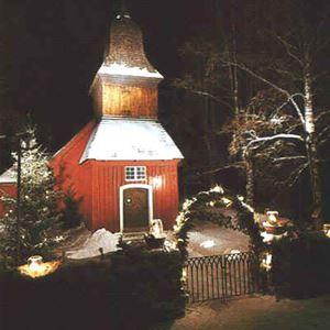 Upplyst kappel med mörker omkring. Snö omkring kapellet.