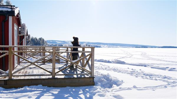 A girl looking out on a frosen lake from the veranda.
