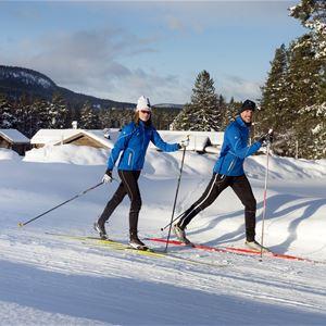 Två skidåkare i skidspåret med snötyngda hustak i bakgrunden.