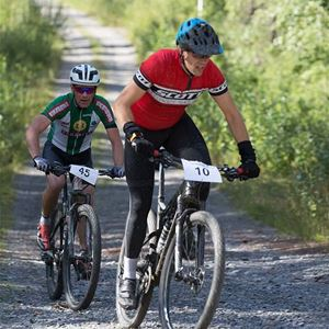 Två cyklister på en grusväg.