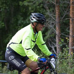 En man cyklar vid skogen.