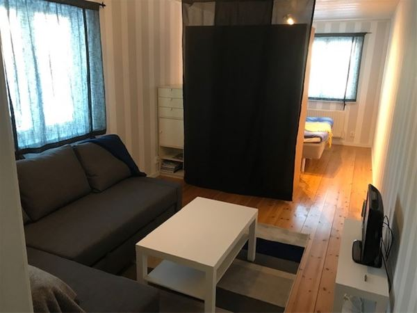 Tv rum med soffa som vetter mot skjutdörr in till dubbelrummet.