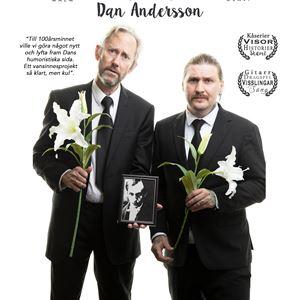 Duon står med en varsin blomma och en håller i ett fotografi på Dan Andersson.