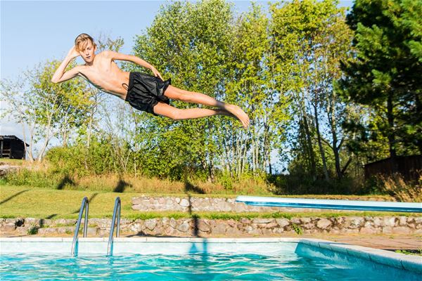 Boy jumping into the outdoor pool.