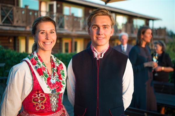 A couple with folklore costume in front of the house.