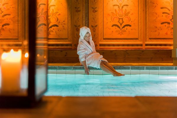 Person in a dressing-gown is sitting on the edge to the indoor pool.