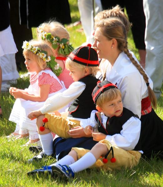 Children in folklore costume and flower wreaths in their hair are sitting on the lawn.