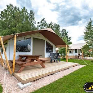 Glampingtent with picnic table under roof.