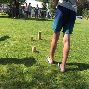 people play games on a lawn and a pair of bare legs in sandals in front.