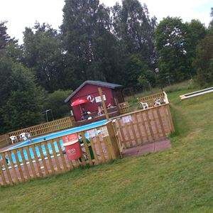 Fenced outdoor pool on a large lawn.