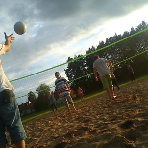 People playing volleyball on the sand.