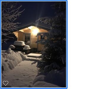 A small cottage in the darkness with light on the entrance and lots of snow on the trees and outdoor furniture.