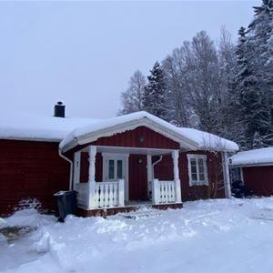 Timmerstuga med vita fönster och snö på marken och taket.