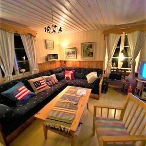 Allrum med blå soffa, soffa och bord i ljust trä.