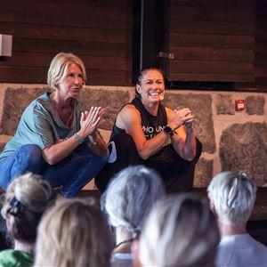 © Sälens Högfjällshotell, Två damer sitter på huk på scenen framför publik.