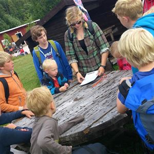 Children gathering around a woodden table and a leader.