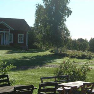 Trädgårdsbord och hus vid Vikarbygården.