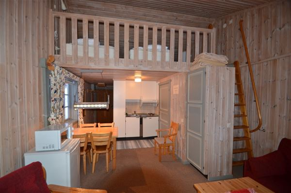 Apartment with refrigerator, microwave, dining table and a loft with beds on.