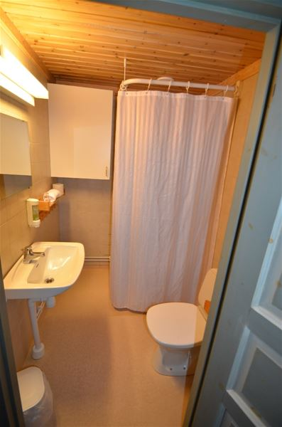 Bathroom with yellow walls, shower wit white curtains, toilet and handbasin.