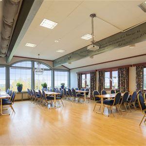 Stor sal med många stora fönster och flera bord med stolar.