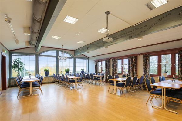 Large room with lots of windows and groups of tables and chairs.