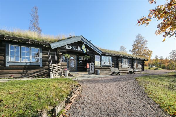 Grey timbered reception-house with grass on the roof.