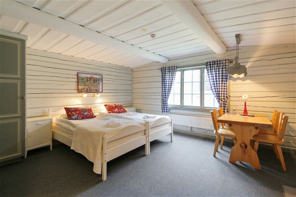 Two single beds put together in front of white timebered walls and dining furniture in pine.