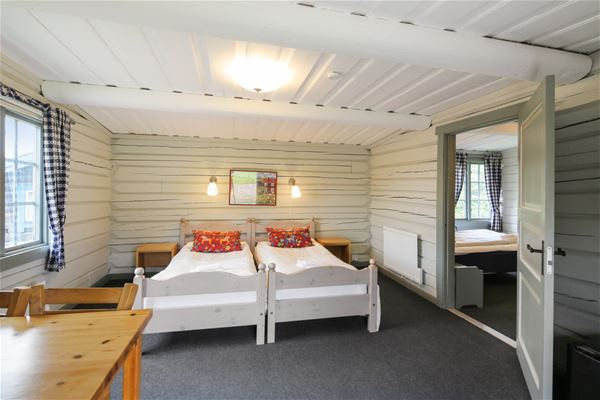 Two single beds with white bedspread and red pillows put together in front of white timbered walls.