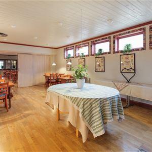 Stort ovalt bord med duk i mitten av en stor sal med matgrupper.