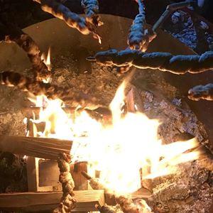 Grillar kolbullar över öppen eld.