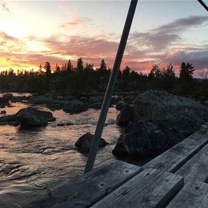 Brygga med staket, vatten och st.enar i solnedgång