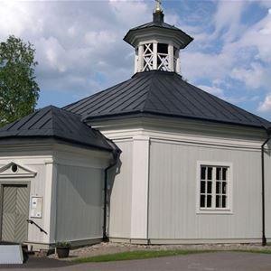 Malingsbo kyrka en liten ljus byggnad med ett litet torn på taket.