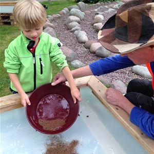 Peter Harström,  © Peter Harström, Ett barn vaskar guld tillsammans med en vuxen.