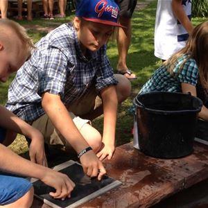 Peter Harström,  © Peter Harström, Barn som sitter på huk och testar med stenhuggning.