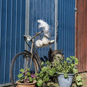 En gammal cykel som står lutande mot en stor blå port, med blomkrukor runt sig.