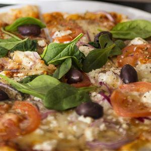 En pizza med basilika,tomat, och oliver som topping.