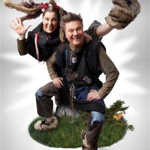 En man och en kvinna som ser glada ut, sitter på en sten på en bit konstgjord gräsmatta, kvinnan har ett ben i luften.